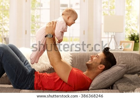 Happy young father lying on sofa, lifting baby girl high up, smiling, having fun. Side view. - stock photo