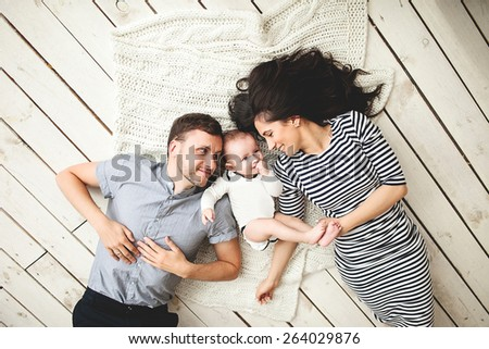 Happy young father, mother and cute baby boy lying on rustic wooden floor - stock photo