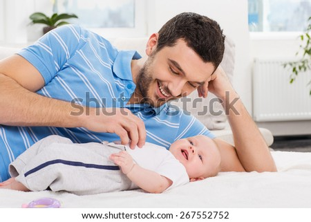 happy young father playing with his little baby - stock photo