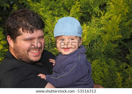 Happy young father playing with his little son in the coniferous forest - stock photo