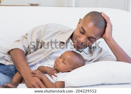 Happy young father with baby son on couch at home in the living room - stock photo