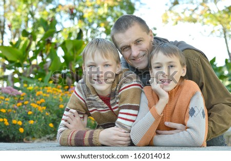 happy young father with his sons on a walk - stock photo