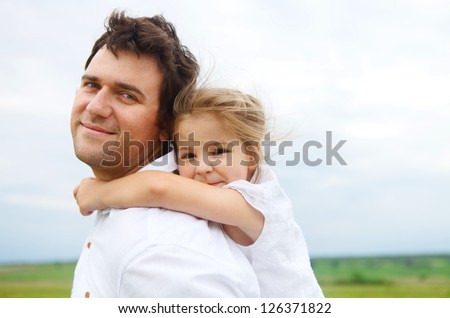 Happy young father with little daughter outdoors - stock photo