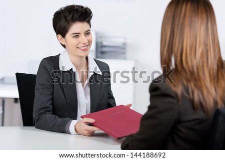 Happy young female candidate giving file to businesswoman at desk in office - stock photo