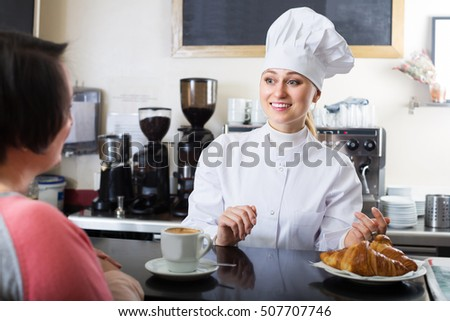 Happy young female cook gladly selling pastry to a customer in the cafeteria