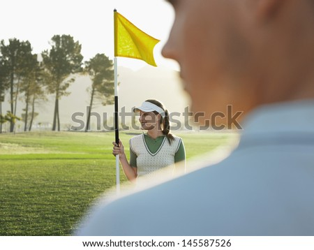 Happy young female golfer holding flag with man in foreground - stock photo