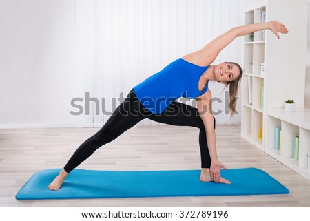 Happy Young Female On Exercise Mat Stretching In Living Room