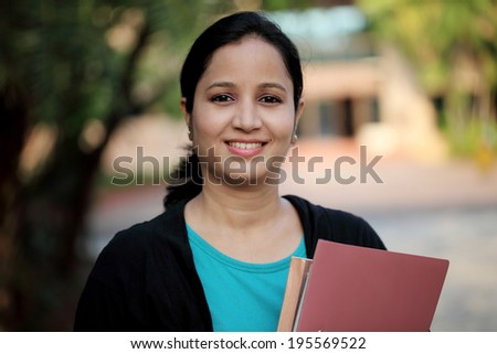 Happy young female student at college campus and carrying books  - stock photo