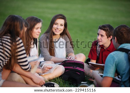 Happy young female student talking with friends - stock photo