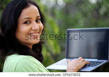 Happy young female student working with tablet computer at campus  - stock photo