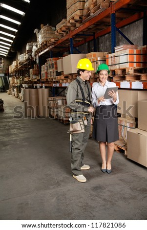 Happy young female supervisor and foreman using digital tablet at warehouse - stock photo