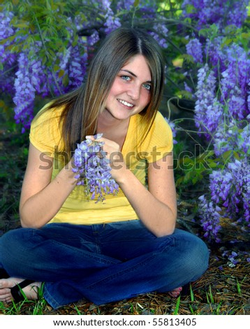 Happy young female teen sits on the ground surrounded by wisteria blossoms.  She holds one grape-like cluster in her hands.