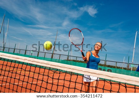 happy young female tennis player returning a ball on a tennis court outdoors - stock photo