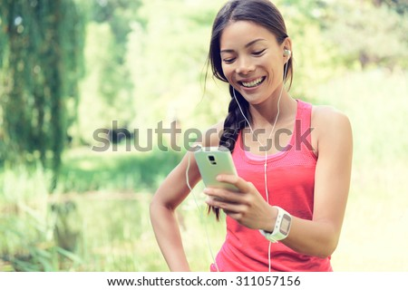 Happy young fit woman using cell phone while listening to music on smartphone. Smiling mixed race Asian / Caucasian female is in sports clothing. She is enjoying music in park. - stock photo
