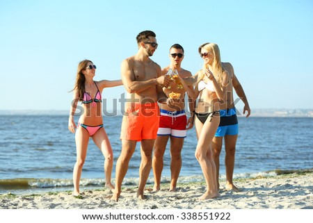 Happy young friends drinking beer at the beach, outdoors