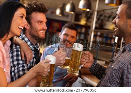 Happy young friends drinking beer, having fun in pub, smiling. - stock photo