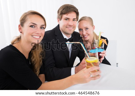 Happy Young Friends Drinking Cocktails In Restaurant