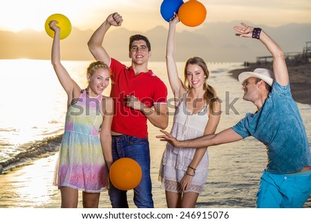 Happy Young Friends Enjoying at the Beach with Balloons During Sunset Time. - stock photo