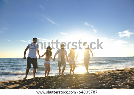 happy young friends group have fun and celebrate while jumping and running on the beach at the sunset - stock photo