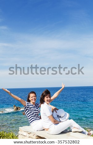 Happy, young friends smiling and looking at camera on seaside promenade.Copy space
