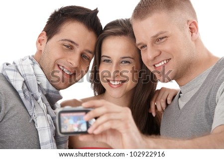 Happy young friends taking photo of themselves, smiling, isolated on white. - stock photo