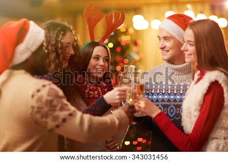 Happy young friends toasting on Christmas party - stock photo