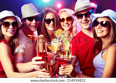 Happy young friends touching the glases with each other at party - stock photo