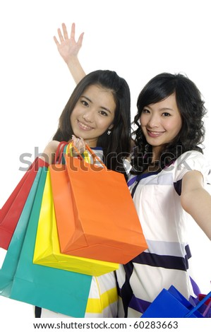 happy young friends with shopping bags standing posing - stock photo