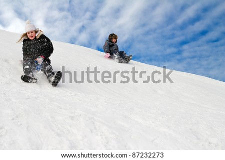 happy young girl and boy are sliding on the snowhill - stock photo