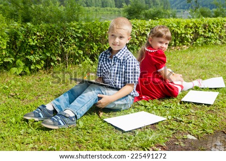 Happy Young girl and boy Writing letter  . Smiling in summer Garden. - stock photo