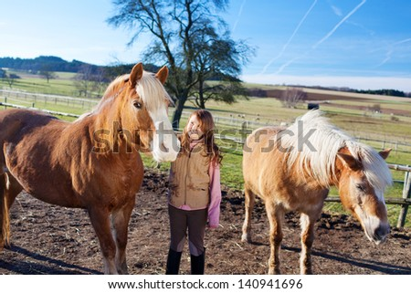 Happy young girl between two horses on a bright sunny day