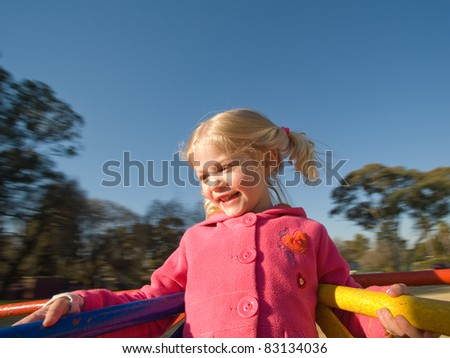 Happy young girl child play on roundabout in park - stock photo