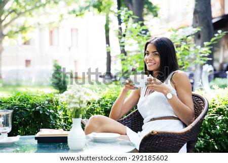 Happy young girl drinking coffee in restaurant outdoors - stock photo