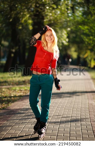 Happy young girl enjoying roller skating in park, active woman outdoor - stock photo