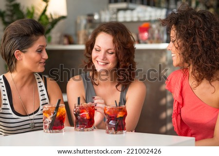 Happy young girl friends having fun in a bar drinking cocktail.  - stock photo