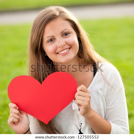 Happy young girl holding red heart on Valentine's Day - stock photo