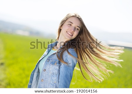 Happy young girl in blue jeans jacket enjoying free time in green field - stock photo