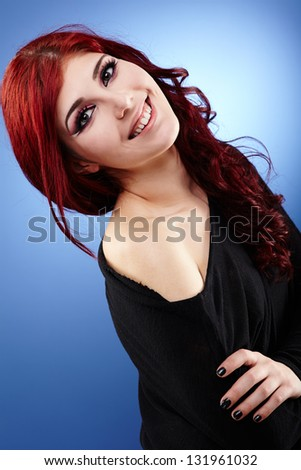 Happy young girl in glamour closeup, on blue background - stock photo