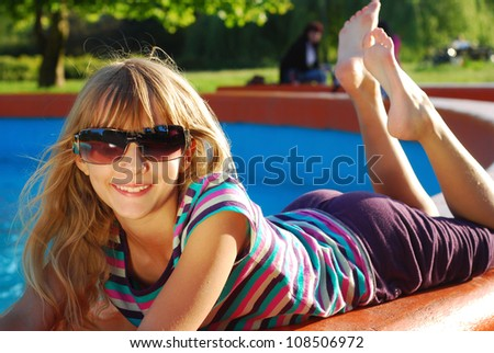 happy young girl in sunglasses lying in the park and relaxing in summer holidays - stock photo