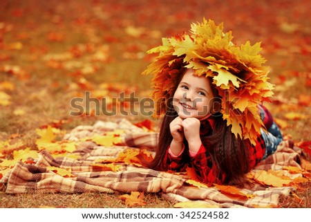 Happy young girl in yellow autumn wreath lying on plaid in park - stock photo