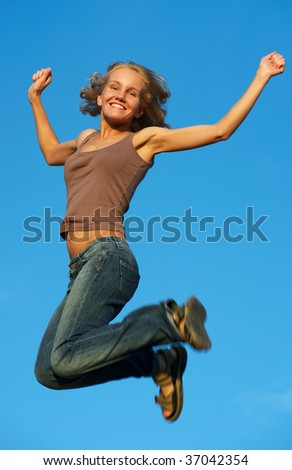 happy young girl jumping against blue sky - stock photo