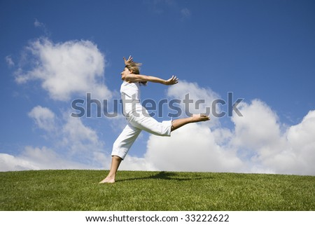 Happy young girl jumping on a beautiful landscape - stock photo