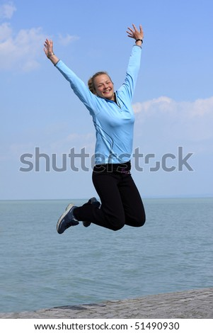 Happy young girl jumping  on the shore