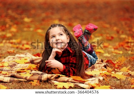 Happy young girl lying on plaid in autumn park