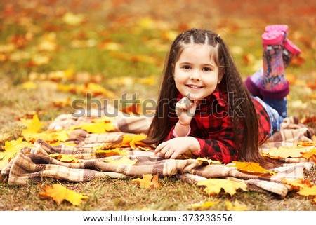 Happy young girl lying on plaid in autumn park - stock photo