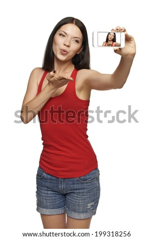 Happy young girl making kiss while taking pictures of herself through cellphone, over white background - stock photo