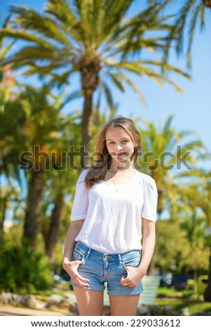 Happy young girl on a tropical beach resort