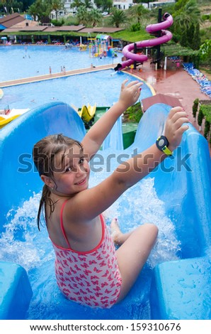 Happy young girl on tropical water slide - stock photo