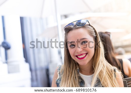 Happy young girl outdoors, front portrait photo with defocused copy space background