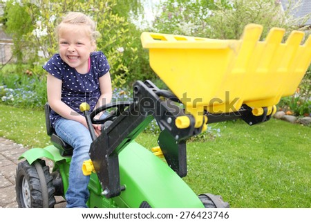 Happy young girl plays on a toy tractor outdoors in the garden - stock photo